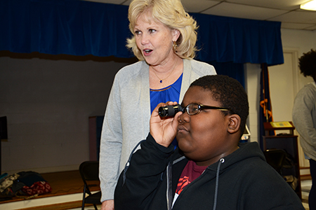 Zacchaeus Reaves tries a monocular with the assistance of Deb Bryan. Ms. Bryan is a teacher of the visually impaired and a Project Magnify consultant.