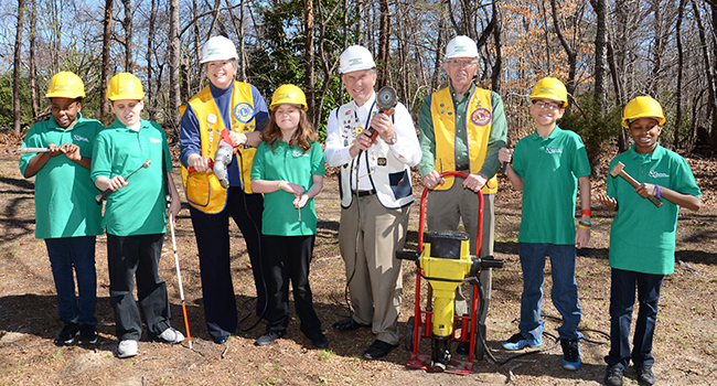 Lions leaders and students posed with tools and hard hats for the groundbreaking invitation.
