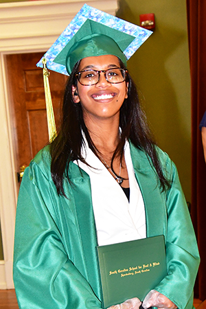 Marirose Fernandes smiles with diploma in hand.