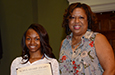 Yasmeen Crute holds a certificate for the McAlister Scholarship with Sara Kollock at Awards Day.