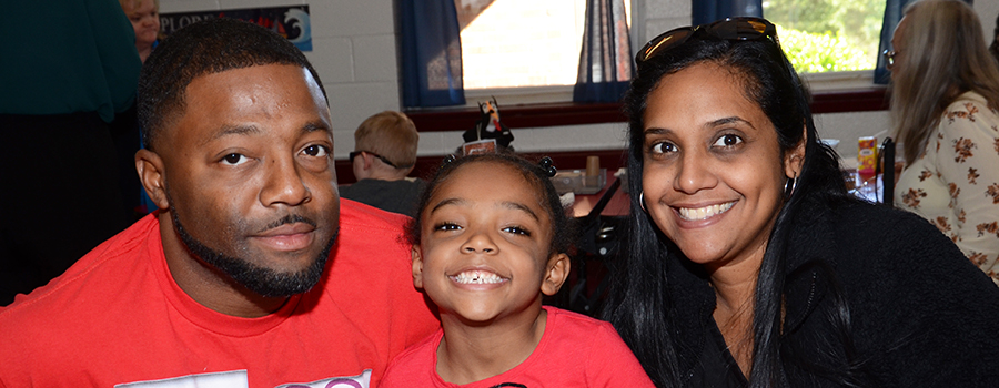 Aaliyah Zimmerman and her parents enjoy lunch in the School for the Blind.