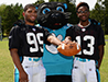 Hermani Mesilien and Drequan Cheeks model the new practice uniforms with Panthers mascot Sir Purr.