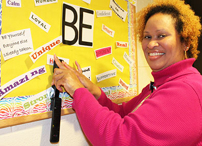Cisha Campbell puts up a bulletin board to encourage good character.