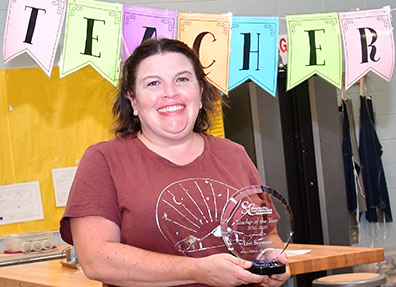 Lori Seymour smiles and shows her Teacher of the Year trophy.