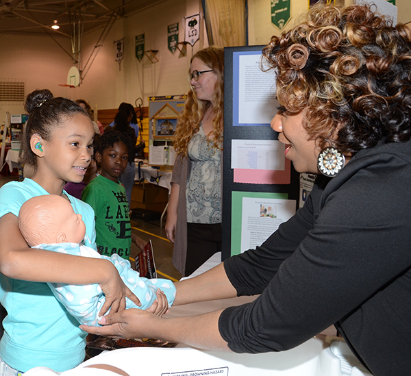 Students practiced holding baby-size dolls as part of the child care booth at the Career Fair.