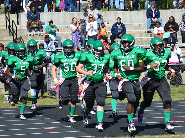 The football team runs on to the field ready take on the opposing team at homecoming.