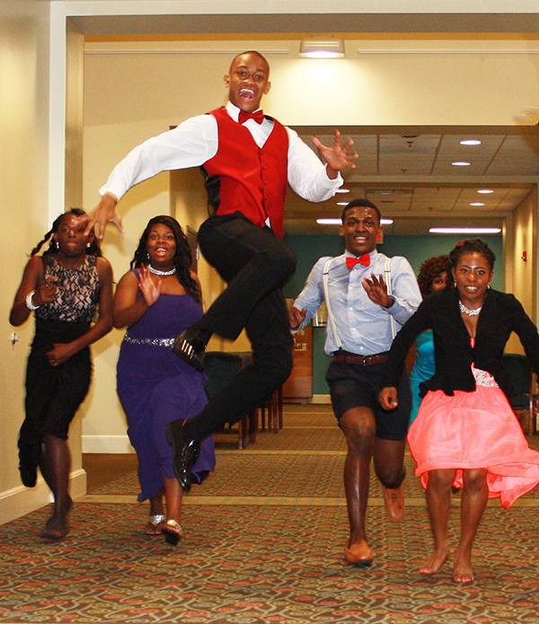 Students run and jump for a fun photo shot at the prom.