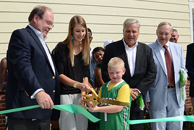 A student takes a leadership role by cutting the ribbon at the Fluor Field House opening event.