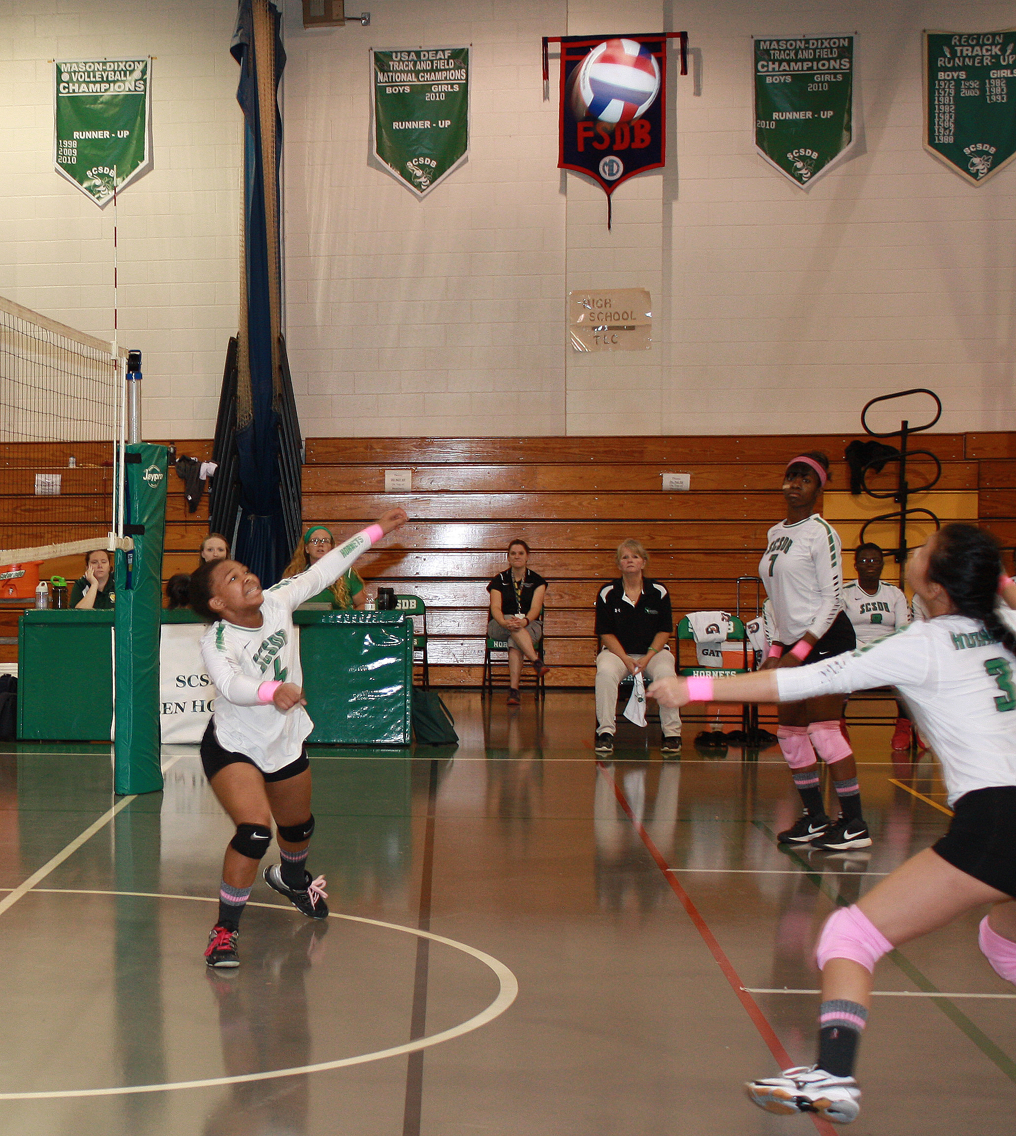 The girls volleyball team keeps their eyes on the ball ready to return it to the visiting team.