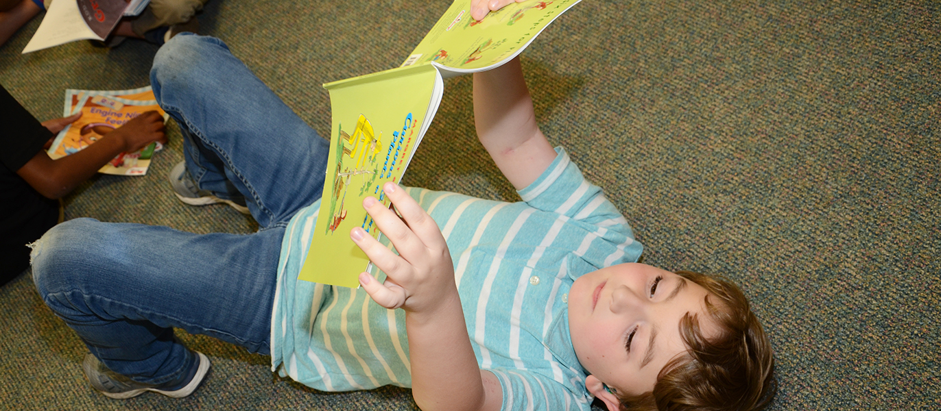 Lucas Coates reads a Curious George book.