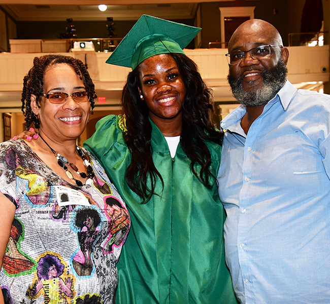 Zion White and her parents pause for a photo after graduation.