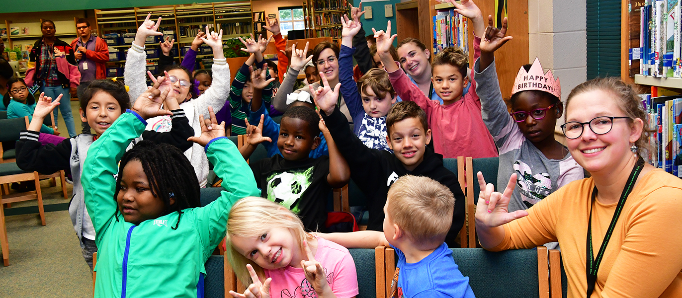 School for the Deaf students smile and show the I Love You hand sign at one of many fun library events.