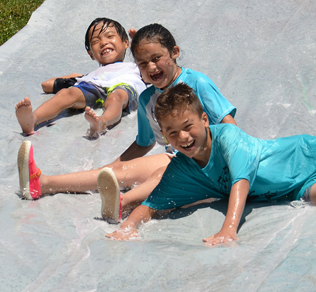 Elementary students enjoy the water slide on field day.