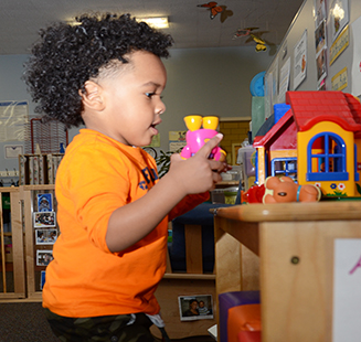 Kelly's Kids enjoy a wide variety of colorful toys including a miniature plastic house.