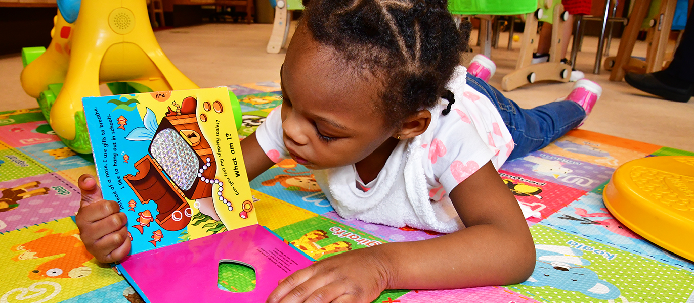 Aaliyah Middleton enjoys reading a colorful book.