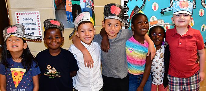 Elementary students model their Johnny Appleseed hats.