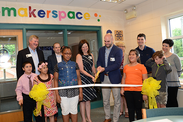 Corie Culp iwth AFL and Joel Douglass with ScanSource cut the ribbon to open Einstein's Workshop.