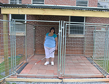 Alyssa Owens uses her cane to navigate the new dog kennel built by Applied Academics students.