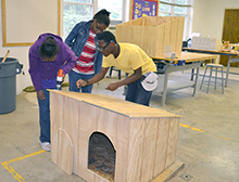 Kadiedra Hay, Aravia Johnson, and Curtis Sparkman drill screws into place for a dog house.