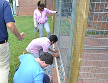 Students put pavers in place along the gate of the new dog kennel.