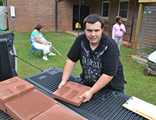 Matthew Cloninger unloads pavers for the floor of the new dog kennel.