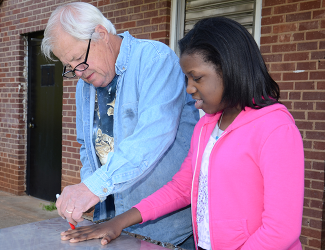 Artist Bob Doster traces student Ari'Yanna Smith's hand onto metal that will be cut out for the larger sculpture.