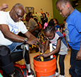 Donald Davis shows Ron 'Ziya Boyd and Tristan Bradley how to set up self-watering planters.