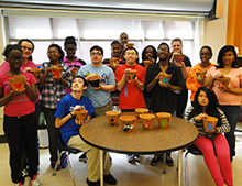 Students show the clay pots they painted as personalized gifts for the Mayor's Committee members.