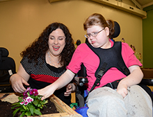 Teacher Susan Mitchell and Kelsey McDougald planted flowers in one of the new wheelchair accessible gardening tables.