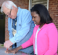 Artist Bob Doster traces student Ari'Yanna Smith's hand onto metal .