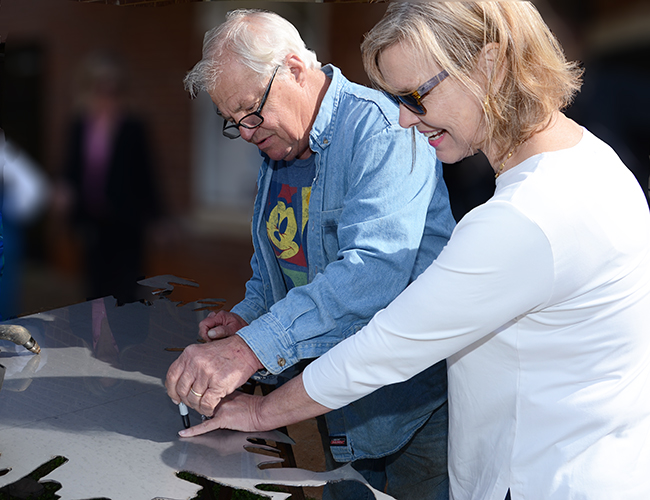 Artist Bob Doster traces Cindy Holland's hand.  Ms. Holland is a member of the school's Board of Commissioners.