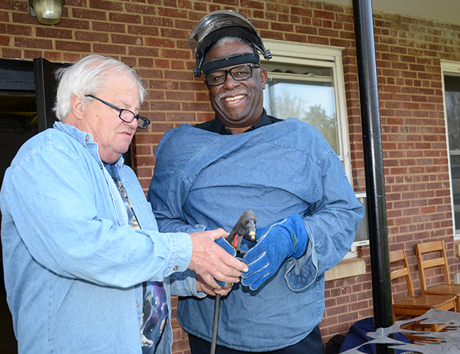Bob Doster shows Tony Fisher, retired city of Spartanburg police chief, how to use the plasma cutter.