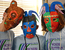 Campers model masks made in fine arts class.