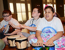Campers played bongo drums during a music session.