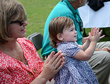 Cynthia Holland, school board member, and her granddaughter, Madeleine Belmont, clap for the team.