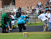 Panthers mascot Sir Purr is welcomed by cheerleaders and high school students.