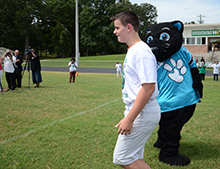 Chase Hanna is greeted by Sir Purr as he walks up to receive his uniform.