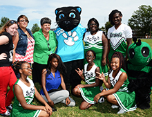 Dr. Page McCraw, interim president, smiles with the cheerleaders and mascots for a group photo.