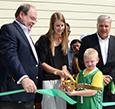 Student Jasper Womick assist Bob Novak and Kristen Taylor with the ribbon cutting.