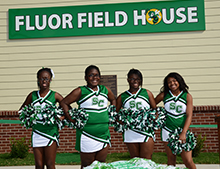 The cheerleaders posed in front of the new Fluor Field House.