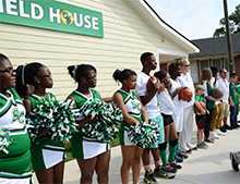 Athletes representing each sport lined up in front of the new field house.
