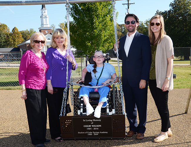 Colby Wilson's family stood by a wheelchair swing named in Colby's memory. Joining them was Katrina Hensley.