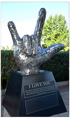 The new sculpture is made up of multiple stainless steel hands that form a large hand showing the I Love You sign.