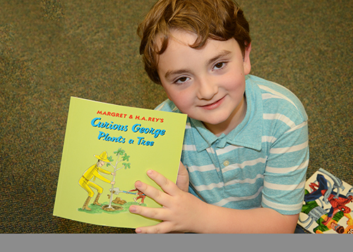 Lucas Coates shows off his new Curious George book.