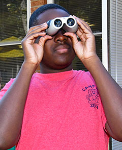 Elijah Gregory tries a set of binoculars during a Project Magnify event.