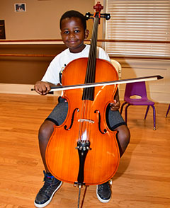 Irvin Kariuki tries out a cello in fine arts class.