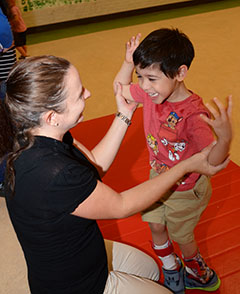 Associate teacher Natasha Earls assists Remy Richardson as he practices standing during a physical therapy session.