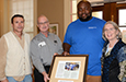 Bill Bomar presents a framed article to Dearon Harrington with Tony Lee and Melinda Osburn.