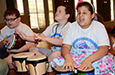 Campers played drums during a music session.